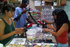 Three volunteers from Derechos Humanos work with Cedric of the Gloo Factory to make a few hundred buttons.