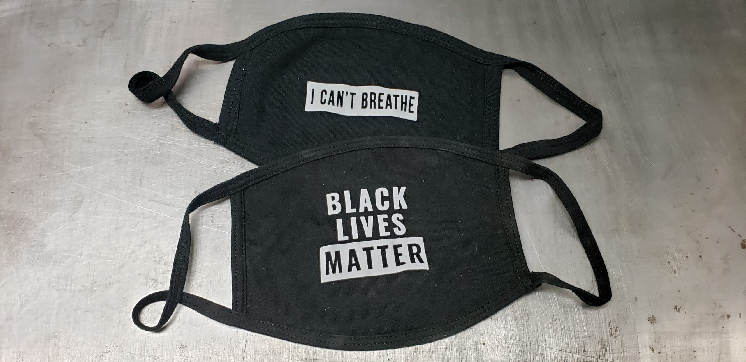 "Two black cloth face masks with the traditional Black Lives Matter design on one and ""I can't breathe"" on the other."