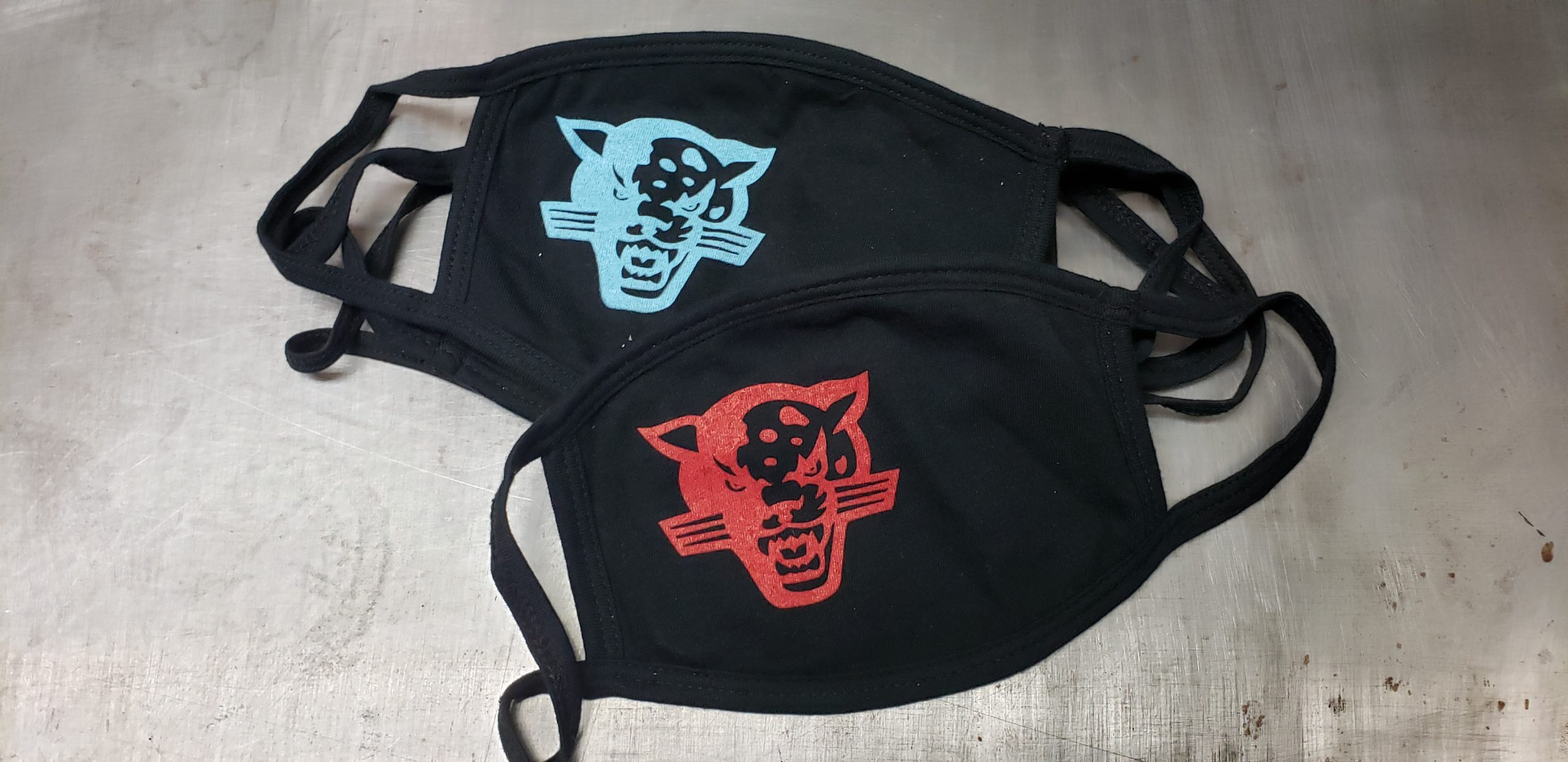 Two black cotton face masks with two different one color color ink union screen designs.