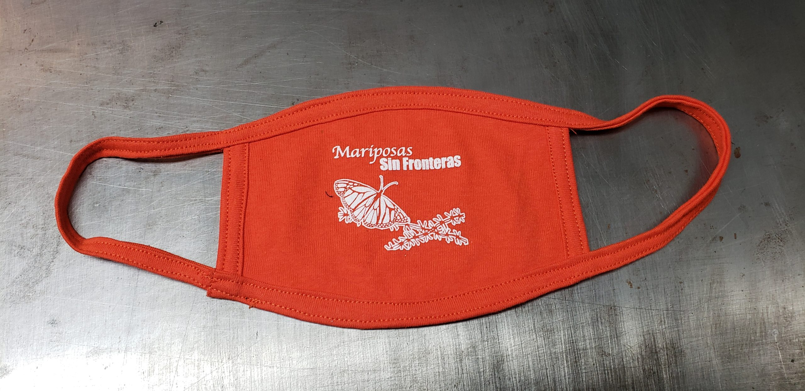 """Orange cotton face mask with union screen printed one color design featuring a butterfly across barbed wiring with text that reads, """"Mariposas Sin Fronteras"""""""