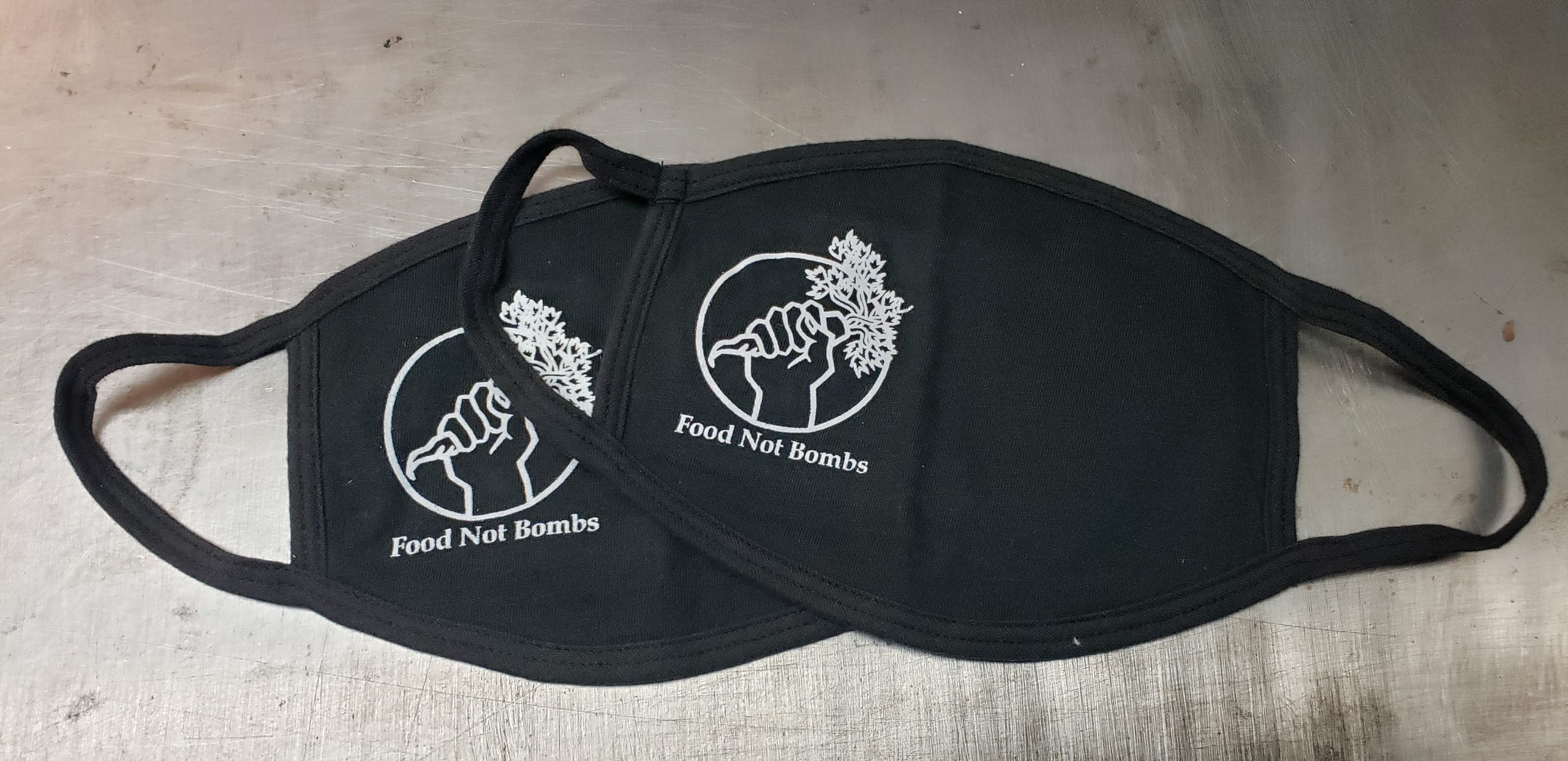 """Two stacked black cotton face masks with union screen printed one color design reading, """"Food Not Bombs"""" with the humanitarian aid organization's logo of a clenched fist raised holding a carrot in an otherwise empty circle"""